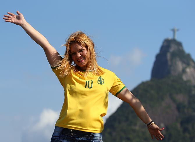 A Brazil fan poses for a photo near the Christ Redeemer in Rio de Janeiro