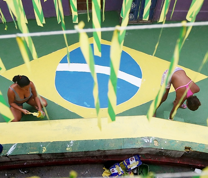 Brazilians paint a section of the Santa Marta shantytown, or 'favela', in Brazilian colors