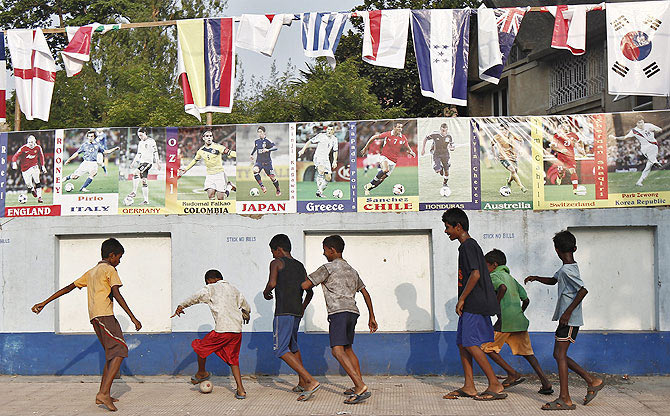 Children play soccer in front of a wall, decorated with pictures of international footballers and their national flags, on the outskirts of Kolkata