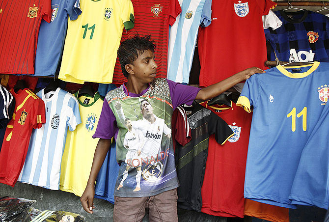 Vendor Mohammad Nihar, 15, arranges World Cup team jerseys at a roadside stall in Kolkata
