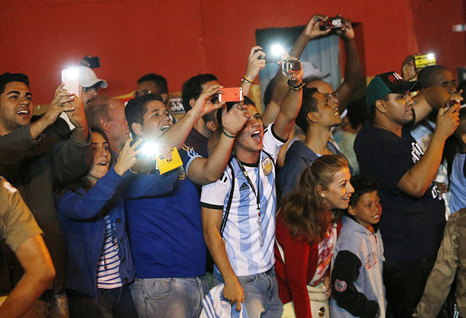 Fans click pictures of Argentina's team bus upon their arrival at Independencia stadium before the start of a training session on Wednesday
