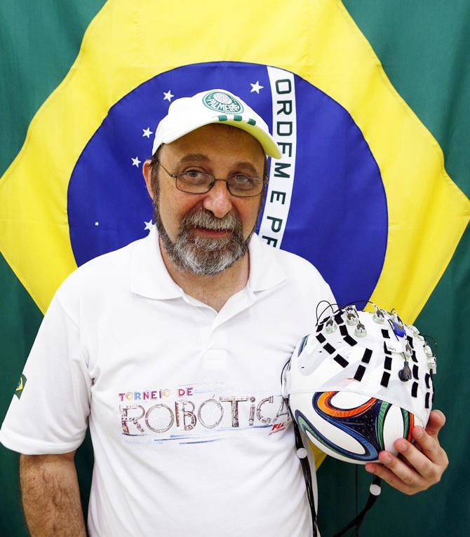 Brazilian neuroscientist Miguel Nicolelis holds a soccer ball covered with a hood of electronic sensors in Sao Paulo