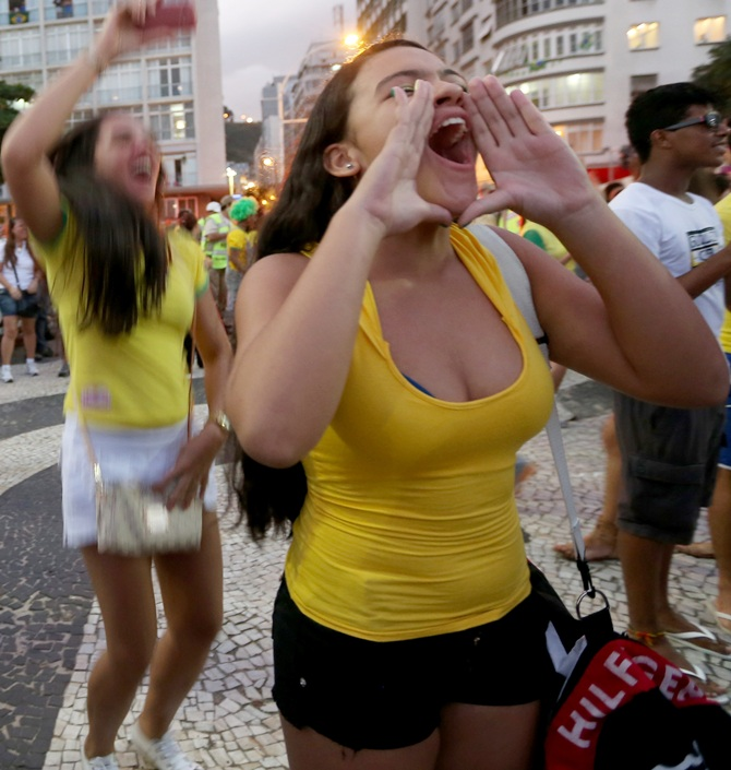 Fans cheer a Brazilian goal as they watch the game on a large-screen