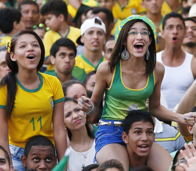 Brazilian soccer fans react while watching the opening match between Brazil and Croatia in a fan zone