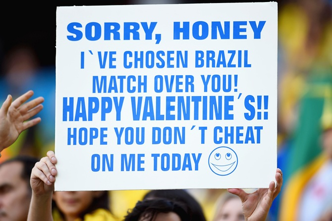 A fan holds up a sign before the Opening Ceremony