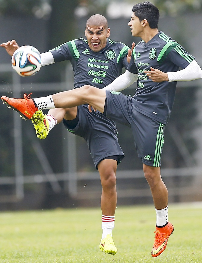 Mexico's national soccer team players Alan Pulido,right, and Carlos Salcido fight for the ball during a training session