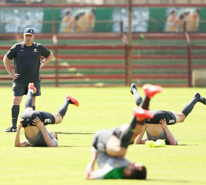 Socceroos coach Ange Postecoglou watches players stretch