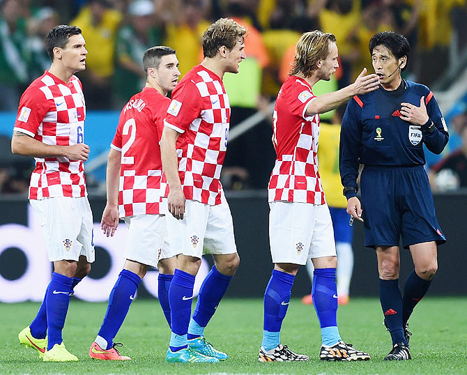 Referee Yuichi Nishimura is pursued by Dejan Lovren, Sime Vrsaljko, Nikica Jelavic and Ivan Rakitic of Croatia after wrongly awarding a penalty on Thursday
