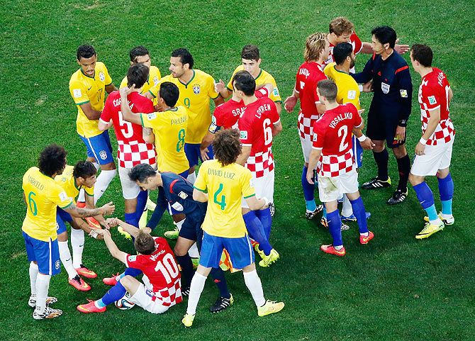 Brazil and Croatia players converge on referee Yuichi Nishimura after a foul and yellow card was shown to Brazil's Neymar during their match  on Thursday