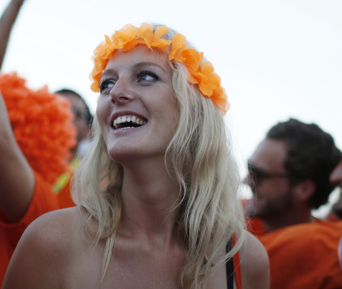A Dutch soccer fan watches the 2014 World Cup soccer match between the Netherlands and Spain on a large screen at Copacabana beach
