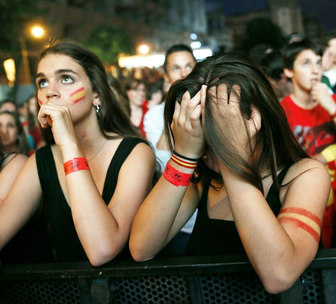 Spain supporters react as they watch the team's 2014 World Cup Group B match against Netherlands on a giant screen