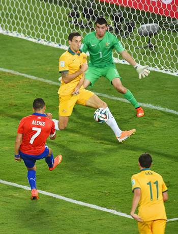Alexis Sanchez of Chile shoots and scores his team's first goal past Australia's Matthew Spiranovic and goalkeeper Mathew Ryan.