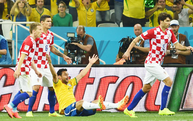 Fred of Brazil sits on the field gesturing for a foul against Dejan Lovren of Croatia during the 2014 FIFA World Cup Brazil Group A match on Thursday