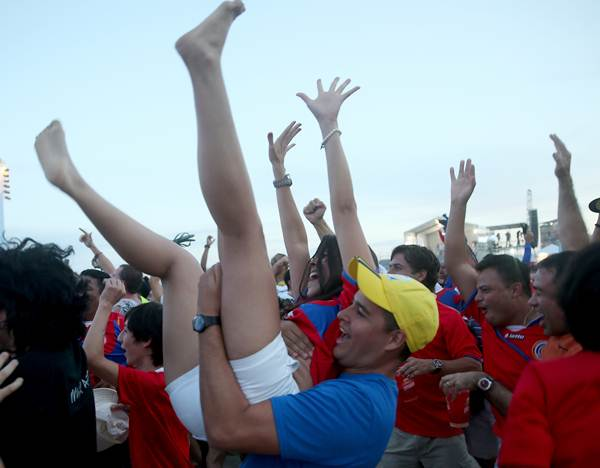 Costa Rican fans react to the first goal their team scored against Uruguay while watching the game on the giant screen showing the match at the FIFA World Cup Fan Fest on Copacabana beach