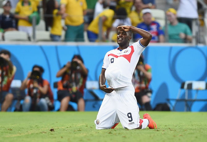 Joel Campbell of Costa Rica celebrates scoring his team's first goal with the ball under his jersey