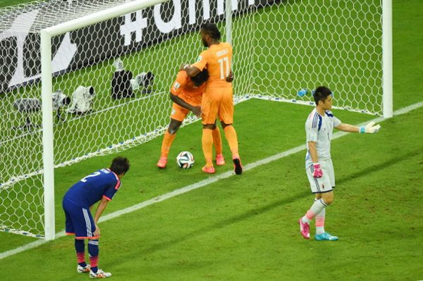Wilfried Bony of the Ivory Coast (second from left) celebrates scoring his team's first goal with Didier Drogba of the Ivory Coast as goalkeeper Eiji Kawashima of Japan reacts and Atsuto Uchida looks on.