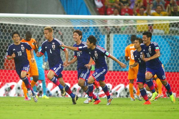 Keisuke Honda of Japan (No 4) celebrates scoring the team's first goal with teammates