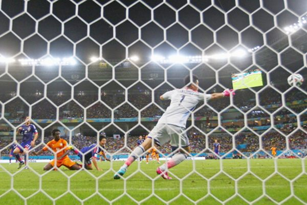 Wilfried Bony of the Ivory Coast scores on a header for his team's first goal past Eiji Kawashima of Japan