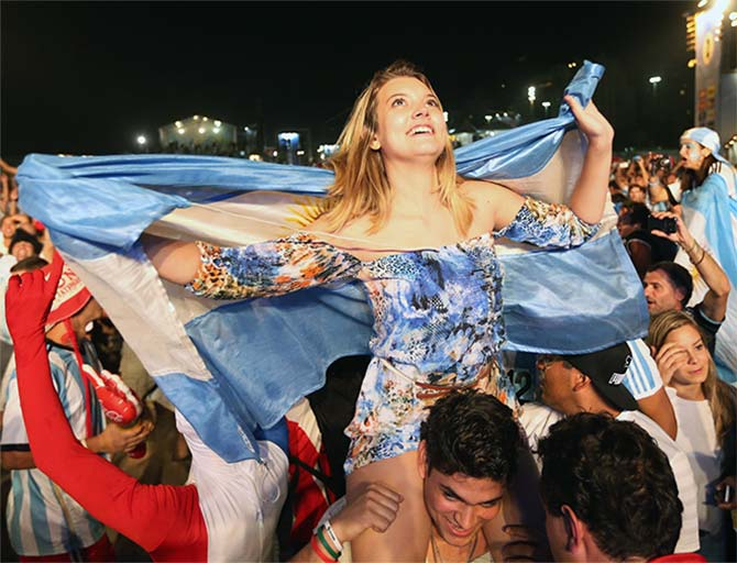 Argentine soccer fans cheer as they watch their team play against Bosnia and Herzegovina on a giant screen