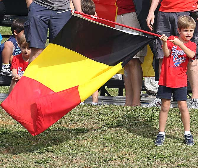 A young Belgium fan waves the country's national flag as he watches the team during a training session