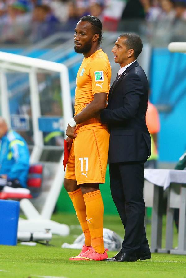 Didier Drogba stands on the sidelines with head coach Sabri Lamouchi during the World Cup Group C against Japan.