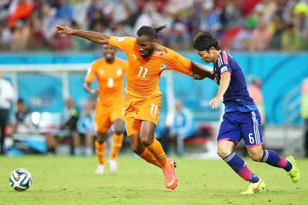 Didier Drogba holds off a challenge by Masato Morishige of Japan