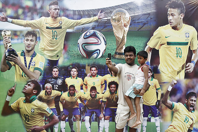 A man takes a selfie with a child, in front of pictures of Brazilian soccer players