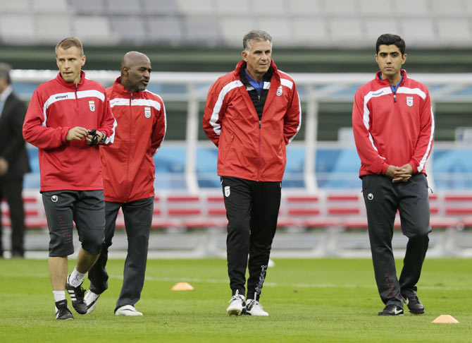 Iran's national soccer team coach Carlos Queiroz (2nd from right) walks with his assistant coaches before a training session at the Arena Baixada soccer stadium in Curitiba on Sunday
