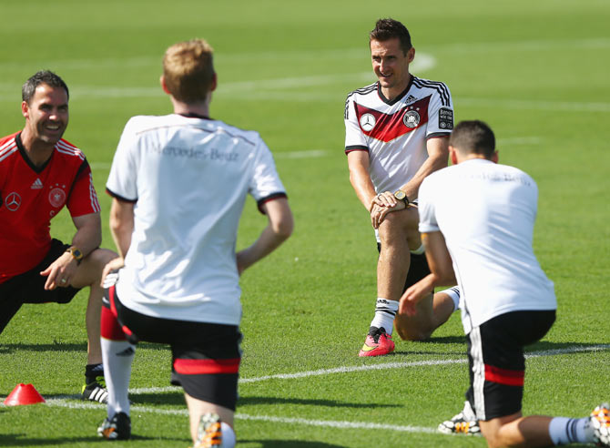 Miroslav Klose (right) stretches during the German National team training session at Campo Bahia in Santo Andre, Brazil