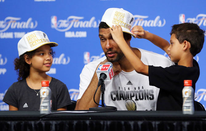 Tim Duncan of the San Antonio Spurs speaks to the media with his children Sydney and Draven after defeating the Miami Heat in Game Five of the 2014 NBA Finals at the AT&T Center on Sunday