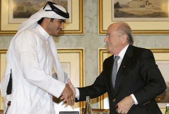 FIFA President Sepp Blatter (right) shakes hands with Qatar's 2022 World Cup Bid Chief Sheikh Mohammed Al-Thani (left) at a news conference