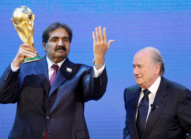 Qatar's Emir Sheikh Hamad bin Khalifa al Thani (left) holds up a copy of the World Cup he received from FIFA President Sepp Blatter