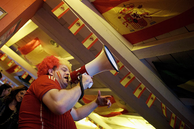 A waiter uses a megaphone to cheer Spanish soccer fans watching their team playing against the Netherlands in a Madrid tavern on Friday