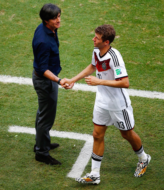 Head coach Joachim Loew of Germany shakes hands with Thomas Mueller as he exits the game after scoring a hat-trick against Portugal in their Group G match at Arena Fonte Nova in Salvador, Brazil on Monday