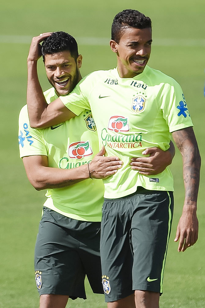 Hulk (left) jokes with Luis Gustavo during a training session of the Brazilian national football team at the squad's Granja Comary training complex in Teresopolis, 90 km from downtown Rio de Janeiro on Saturday