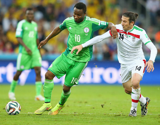 John Obi Mikel of Nigeria and Andranik Teymourian of Iran vie for possession on Monday