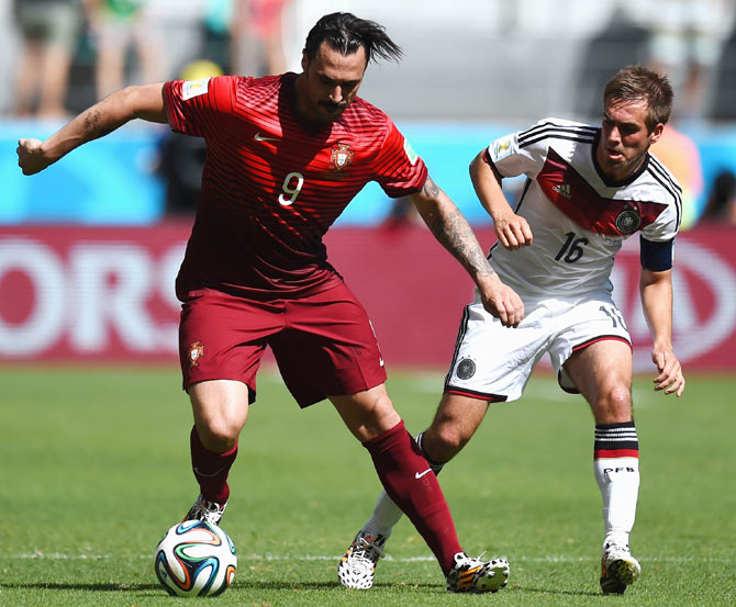 Hugo Almeida of Portugal dribbles past Philipp Lahm of Germany during theirWorld Cup Group G match at Arena Fonte Nova in Salvador on Monday