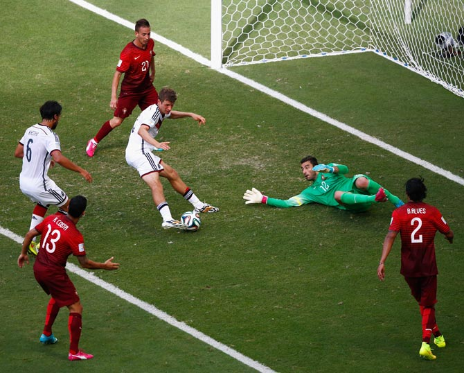 Thomas Mueller of Germany (centre) scores his team's fourth goal and completes his hat trick past Portugal goalkeeper Rui Patricio