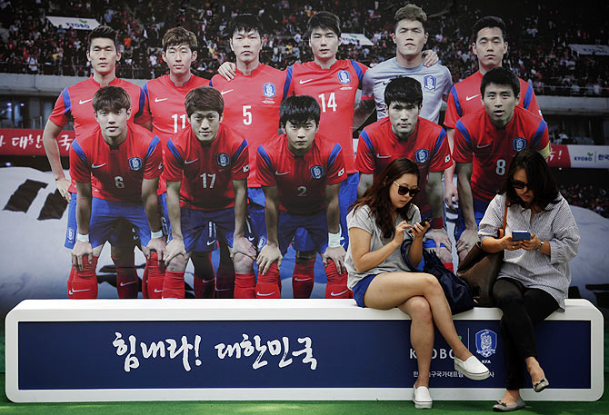 Women use their mobile phones in front of a board with a picture of the South Korean national soccer team in Seoul on Tuesday