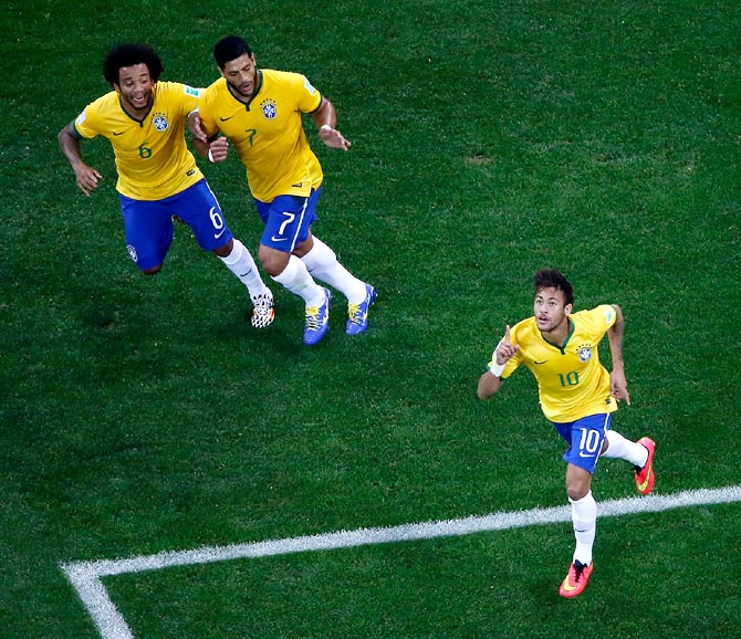 Neymar of Brazil (right) celebrates his goal with his team mates Marcelo (left) and Hulk (C) during the 2014 FIFA World Cup Group A match against Croatia at Arena de Sao Paulo.