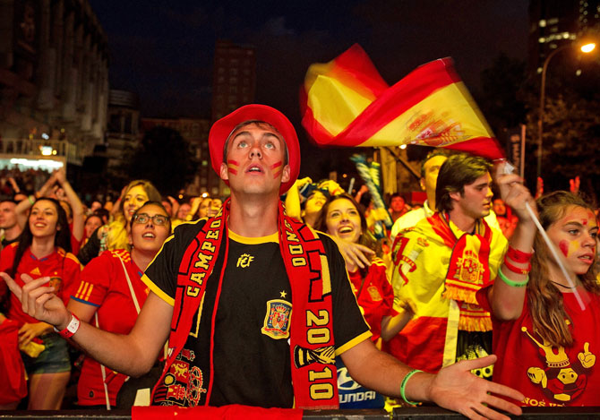 A Spanish soccer fan watches as his team plays against the Netherlands