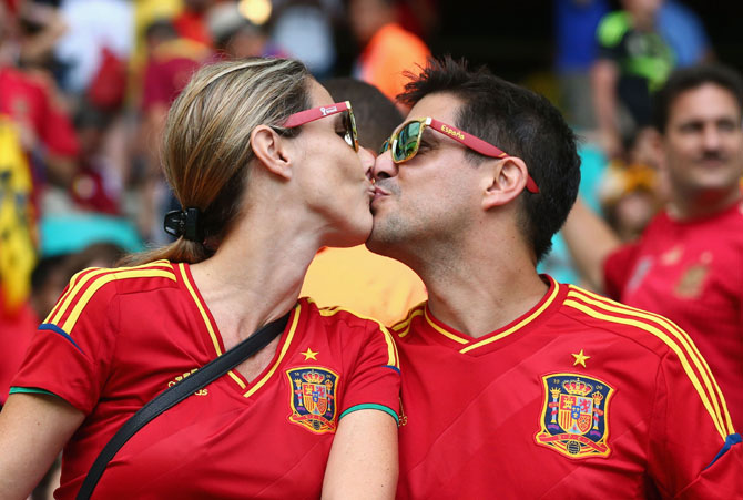 Two Spain fans kiss before the Group B match against Netherlands at Arena Fonte Nova