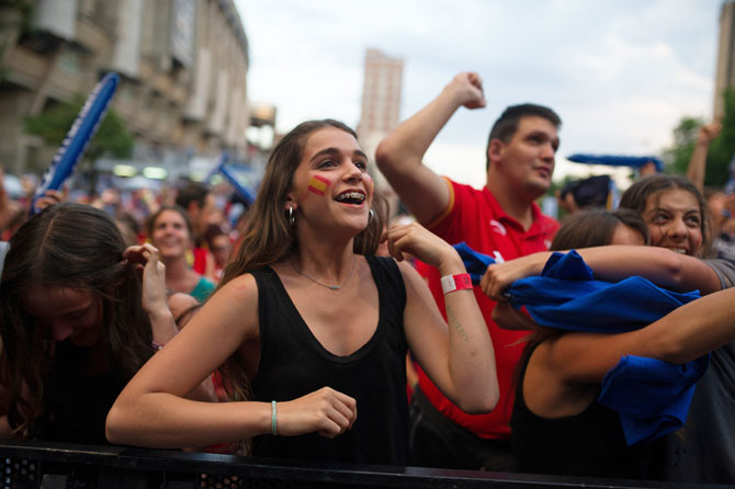 A Spanish soccer fan celebrates while watching Spain score a goal against the Netherlands
