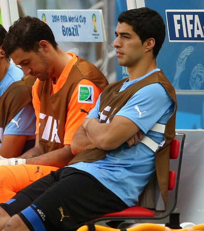 Luis Suarez (right) sits on the bench
