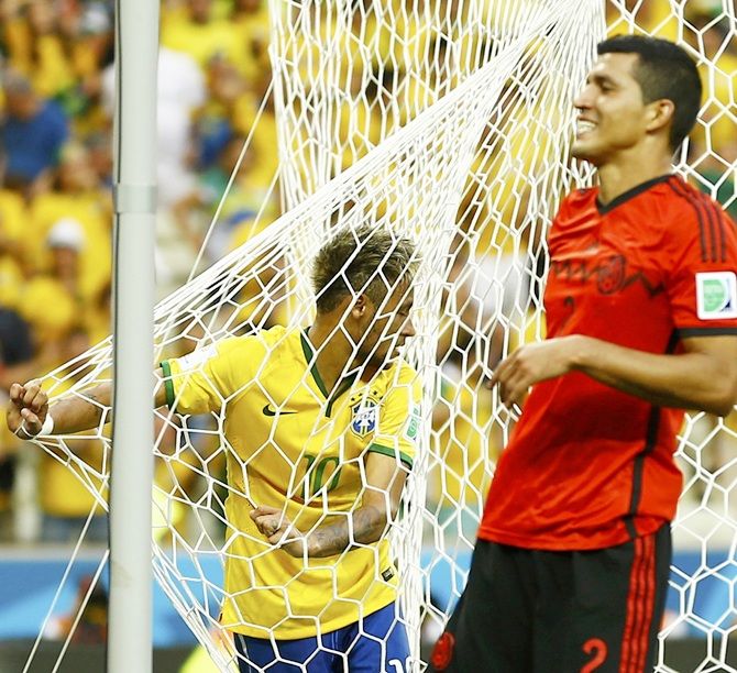 Brazil's Neymar holds the net after a failed attempt at the goal, as Mexico's Francisco Rodriguez smiles
