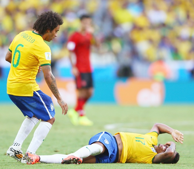 Luiz Gustavo of Brazil lies on the field as Marcelo stands over