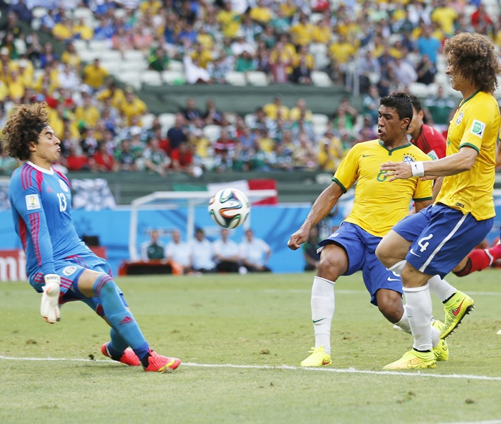 Mexico's Guillermo Ochoa, left, makes a save in front of Brazil's Paulinho and David Luiz