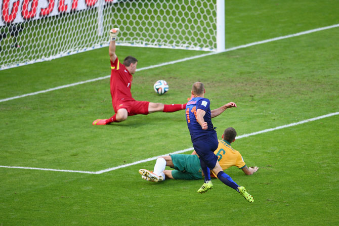 Arjen Robben of the Netherlands shoots and scores his team's first goal past goalkeeper Mathew Ryan of Australia