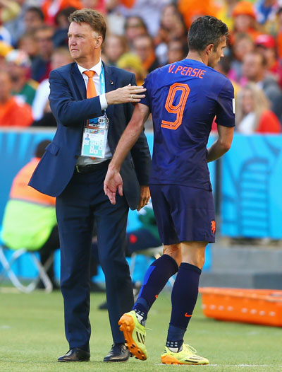 Robin van Persie of the Netherlands reacts with head coach Louis van Gaal as he exits the game