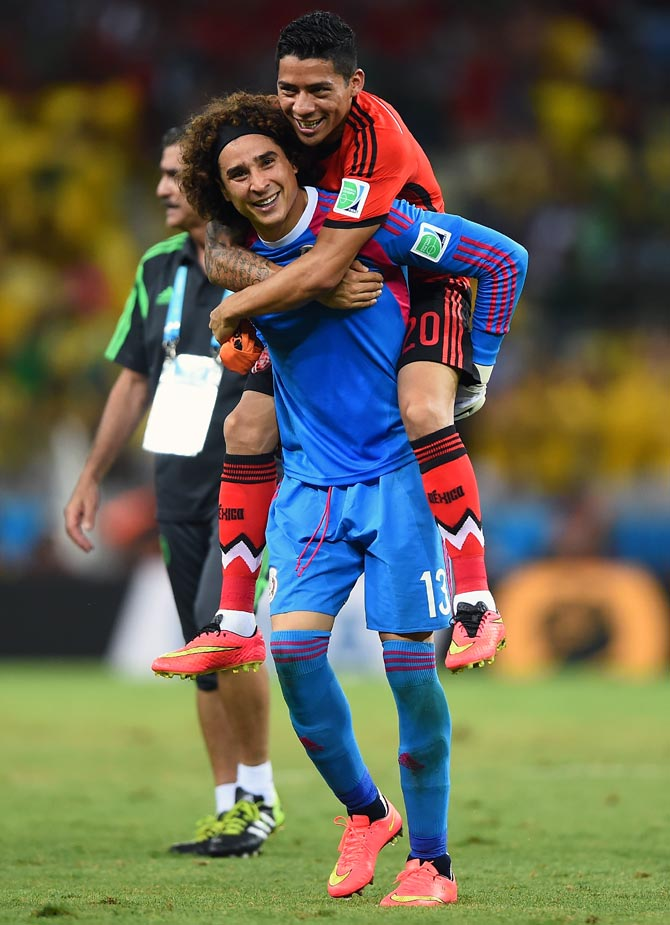 Goalkeeper Guillermo Ochoa of Mexico celebrates with Javier Aquino after their 0-0 draw with Brazil